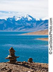 Buddhist stone pyramid at morning Tso Moriri Lake. Altitude 4600 m. View at Himalaya mountains range with Gya peak 6794 m. India, Ladakh
