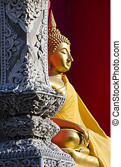 A vertical image of a statue of Buddha in sitting meditation at a Buddhist temple in Chiang Mai Thailand
