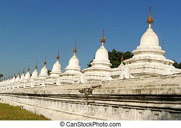 Buddhist towers in Myanmar - Row of historic white buddhist...