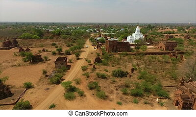 Wide, high-angle push in dolly shot of historic temples and stupas in the desert plains of Bagan, Myanmar