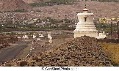 A wide steady shot of Buddhists sacred worshiping temples with part of a ruined wall made of piles of stone.