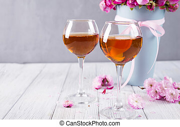 Buds of red roses and glases of wine on wooden background,...