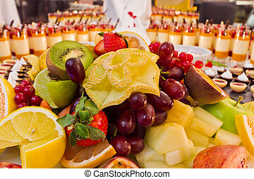 A table of fruit and dessert buffet.