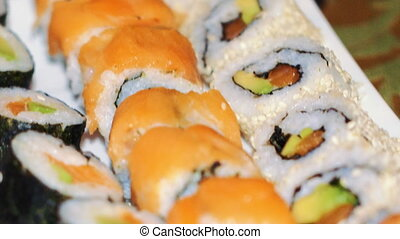 buffet, sushi dishes and rolls are on the table