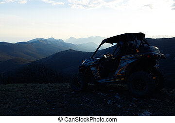 Buggy machine parked in mountains at sunset