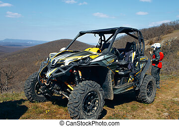 Buggy parked in mountains and driver in sport equipment standing behind