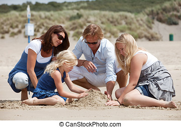 Buidling a sandcastle together - Attractive family sitting...