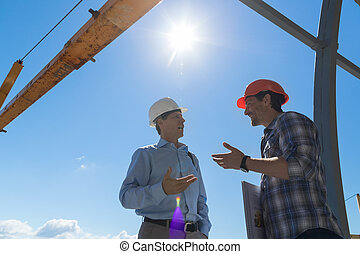 Builder And Business Man Discussing Project Meeting Outdoors On Buiding Constuction Site