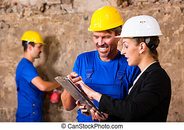 Builder and supervisor on construction site