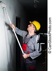 Builder applying paint on a wall with roll