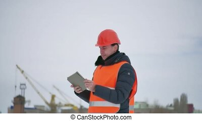 builder architect man in helmet with tablet on construction site. construction industry worker in winter building a house lifestyle