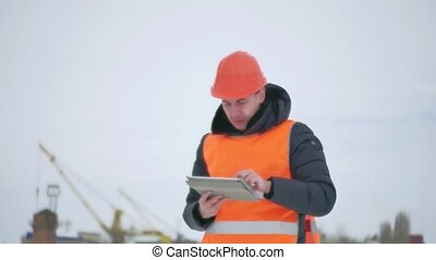builder architect man in helmet with tablet on construction...