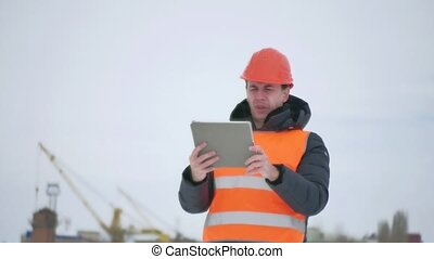 builder architect man in helmet with tablet on construction site. construction industry worker in winter building a house outdoors lifestyle