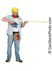 Builder assessing a piece of wood