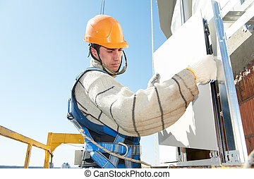 builder at aerated facade tile installation - worker...