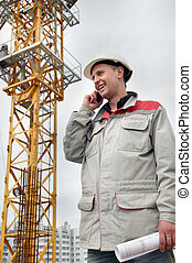 builder at construction site with phone