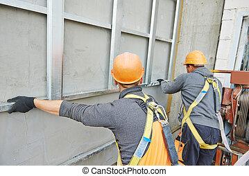 builder at facade construction work - worker builder making...