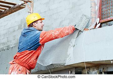 Builder at facade plastering works