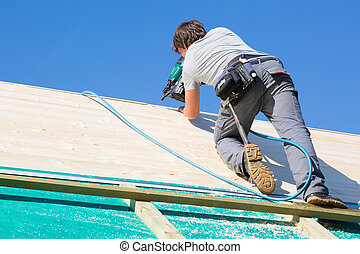 Builder at work with wooden roof construction.