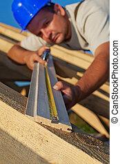 Builder carpenter measuring wood planck