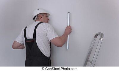 Builder check level near wall in apartment
