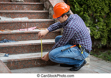 builder checking stairs height by measuring tape - Young...