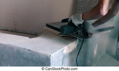 Builder cuts the board with a circular saw on the house...