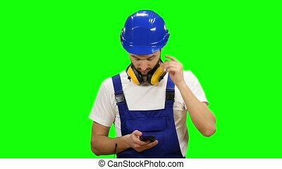 Builder dials a message on his phone. Green screen - Builder...