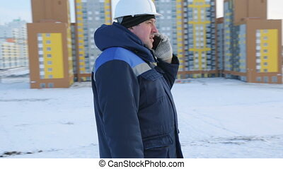 Builder engineer at construction site talking on phone