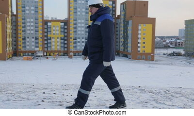 Builder engineer walking to construction site
