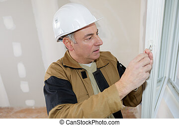 builder fixes hold down plastic bracket to the window