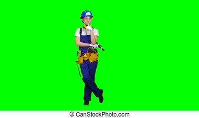 Builder girl in a helmet and overalls holds a drill in her hands . Green screen