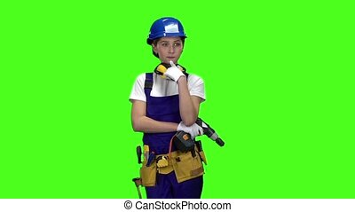 Builder girl in a helmet and overalls holds a drill in her hands . Green screen. Slow motion