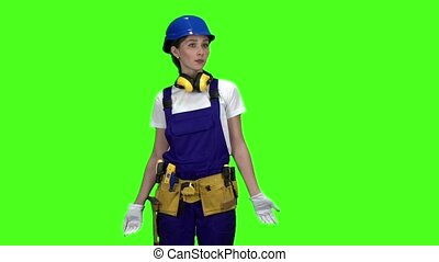 Builder girl in a helmet and suit looks around . Green...