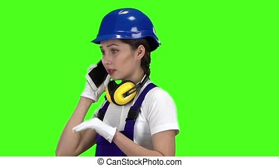 Builder girl in a helmet talking on the phone . Green screen. Slow motion