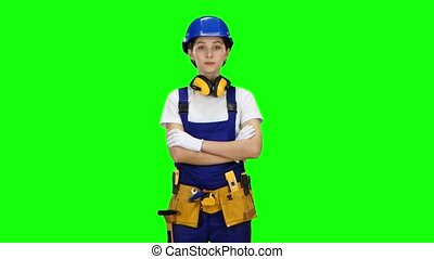 Builder girl in the helmet raises her head and starts to...