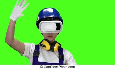 Builder girl in virtual reality glasses plays an interesting game. Green screen. Slow motion