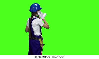 Builder girl stands sideways holding a drawing in her hands and talking on the phone . Green screen. Slow motion