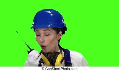 Builder girl wearing a helmet talks on the walkie talkie. Green screen. Slow motion