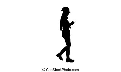 Builder girl with long hair in a helmet goes . Silhouette. White background . Side view