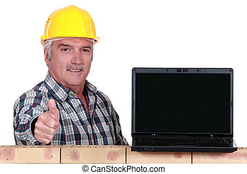 Builder giving the thumbs up to a laptop with a blank screen