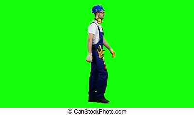 Builder goes to the object with a helmet and tools. Green screen. Side view