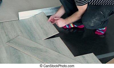 builder guy hands installing wooden board on floor. Static...