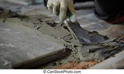Builder hand levelling concrete with trowel, spreading poured.