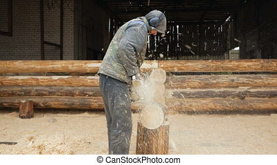 Builder handles wooden timber chainsaw. Against the background is part of the future of the house made of wooden beams, slow motion