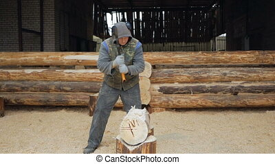 Builder handles wooden timber with axe. Against the background is part of the future of the house made of wooden beams, slow motion