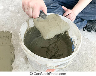 Builder hands with a metal spatula kneads in a large white plastic construction bucket plaster, tile glue, cement for the repair of an apartment, house, leveling the walls and pouring screed