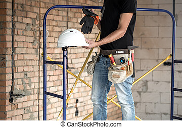 Builder handyman with construction tools. House and house renovation concept.