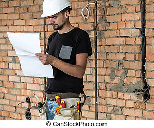 Builder handyman with construction tools, looking at the drawings on the construction site.