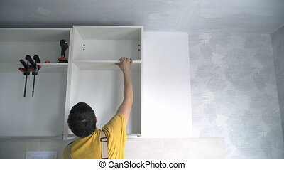 Builder hang a wall Cabinet.